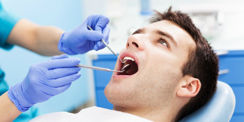 Doctor carrying out dental checkup on a man