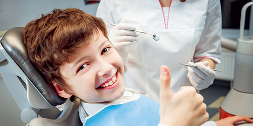 Smiling boy on the dentist's consultation chair showing thumbs up