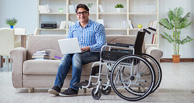 Disabled man sitting on a sofa with laptop and wheelchair next to him