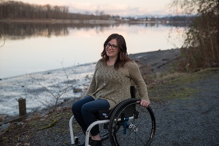 Woman in a wheelchair outside by some water